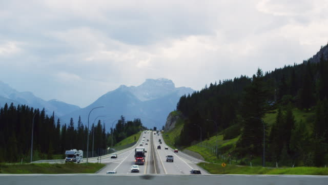 driving over an overpass while underneath vehickles drive along the trans-canada highway under an overcast sky with forests and the canadian rockies in the background in alberta, canada - major road stock videos & royalty-free footage
