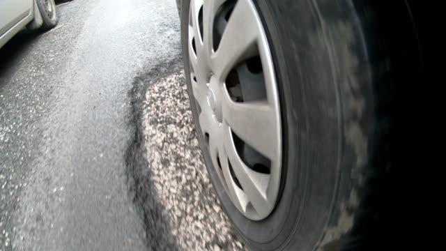 vídeos y material grabado en eventos de stock de 4k: conducir sobre baches en carretera dañada, vista desde el neumático - desigual con textura