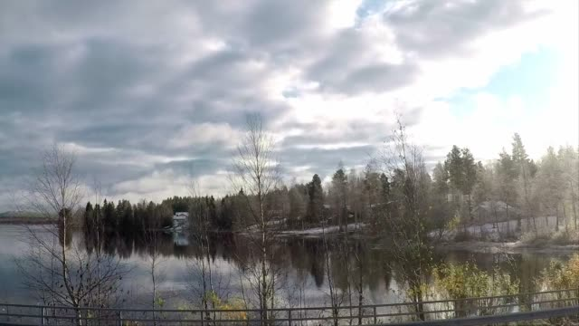 vidéos et rushes de driving past a forest with sun shining through the trees with snow, car travel, road trip in finland - arbre sans feuillage