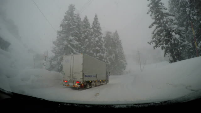 Driving past a truck stuck in deep snow during a blizzard in northern Japan