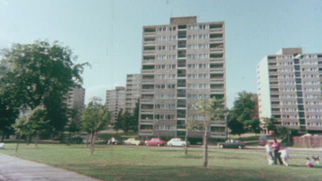 1976 POV Driving past high-rise tenement housing community in park-like setting / United Kingdom
