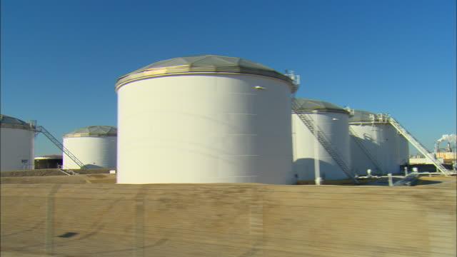SIDE POV Driving past large oil storage tanks at refinery complex, Ponca City, Oklahoma, USA