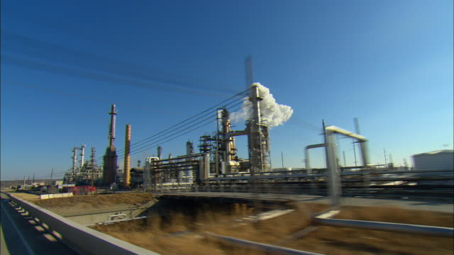pov driving past large refinery complex, ponca city, oklahoma, usa - oklahoma stock-videos und b-roll-filmmaterial