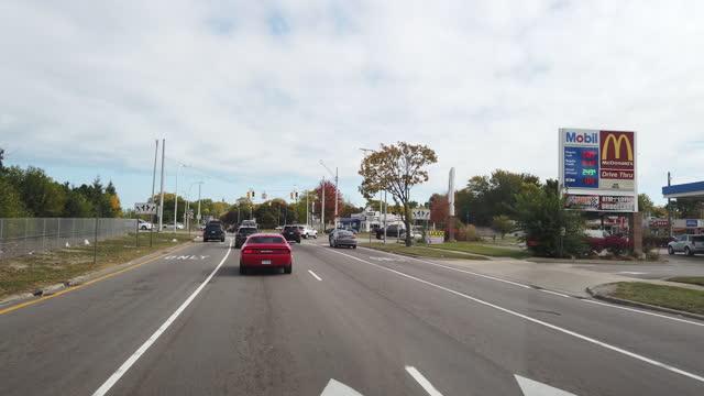 vídeos de stock e filmes b-roll de driving past mobil gas station and mcdonald's in detroit amid the 2020 global coronavirus pandemic. - outdoor pursuit