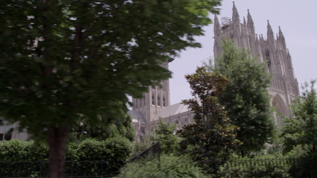 pov driving past national cathedral and other buildings / washington dc, united states - cathedral stock videos & royalty-free footage
