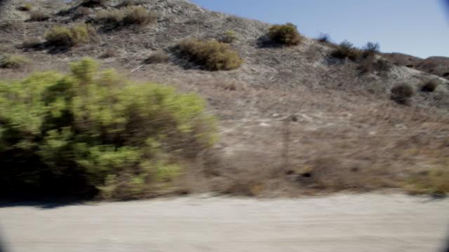 stockvideo's en b-roll-footage met pov driving past rocky mountains / santa clarita, california, united states - santa clarita