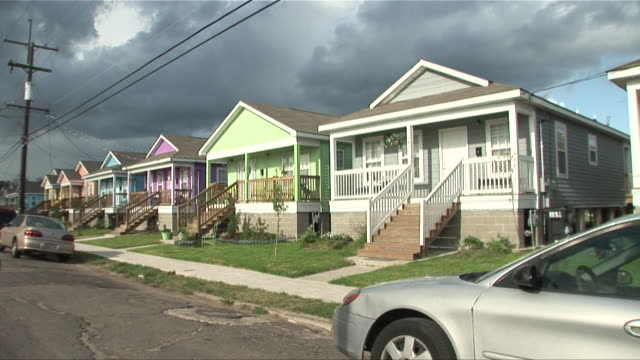 PASSENGER POV driving past row of new, brightly painted houses in the Ninth Ward/ New Orleans, Louisiana