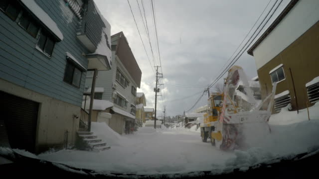 Driving past specialist snow clearing machine on highway as winter storm dumps heavy snow in Japan