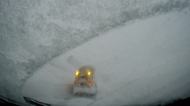 Driving past specialist snow clearing machine on highway as winter storm dumps heavy snow