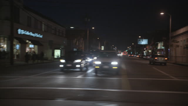POV Driving past stores on urban streets at night / Los Angeles, California, United States