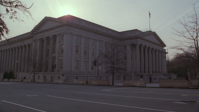 la suv driving past u.s. treasury building at dawn / washington, d.c., united states - 財務省ビル点の映像素材/bロール