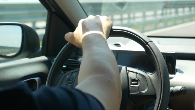 driving pov of a hand on a steering wheel. - slow motion - lenkrad stock-videos und b-roll-filmmaterial