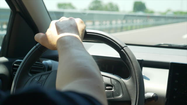 driving pov of a hand on a steering wheel. - slow motion - automobile video stock e b–roll