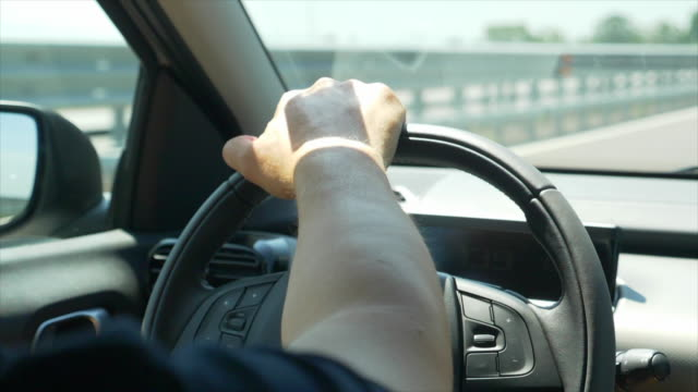 driving pov of a hand on a steering wheel. - slow motion - steering wheel stock videos & royalty-free footage