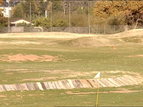 driving range, scattered golf balls all over dry grass/range, across range, cluster of golf balls & flag marker . - driving range stock videos & royalty-free footage
