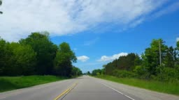 Driving Rural Countryside During Bright Summer Day.  Driver Point of View POV Along Beautiful Sunny Country Road.