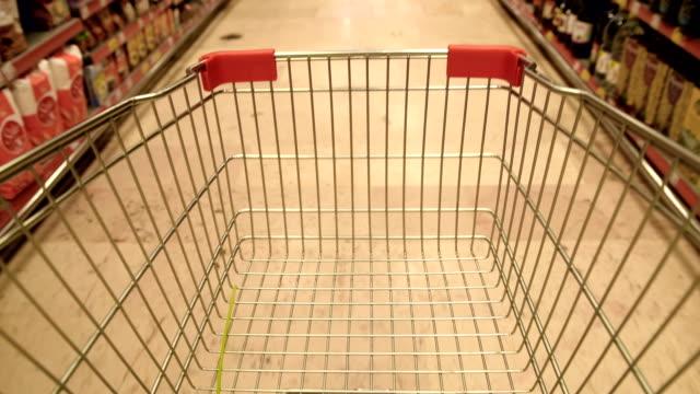 vídeos de stock, filmes e b-roll de carro de compra de condução no supermercado - resolução 4k - imagem em movimento loopable - carrinho de compras