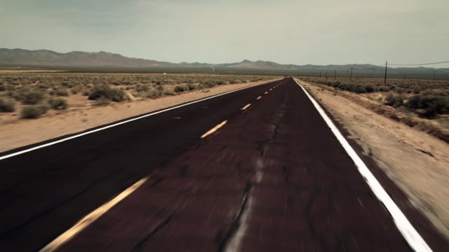 driving shot down empty, cracked desert road - empty road stock videos and b-roll footage