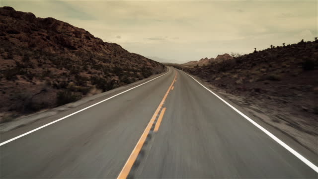 driving shot down lonely desert road (fast motion) - empty road stock videos and b-roll footage