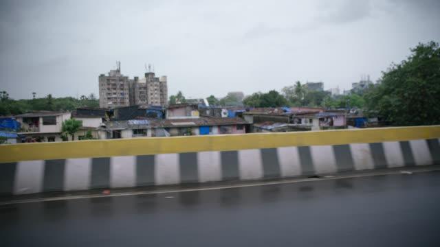 vídeos de stock, filmes e b-roll de slo mo. driving shot down rainy mumbai road overlooking poor neighborhood. - perspectiva do passageiro