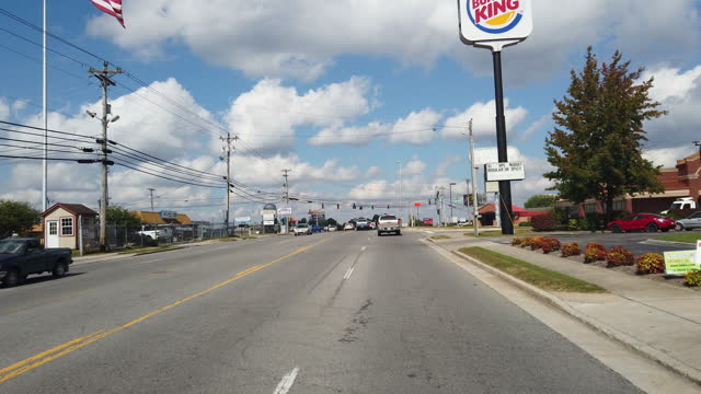 driving shot of burger king fast food restaurant and american flag in a small town in tennessee amid the 2020 global coronavirus pandemic. - catena di negozi video stock e b–roll