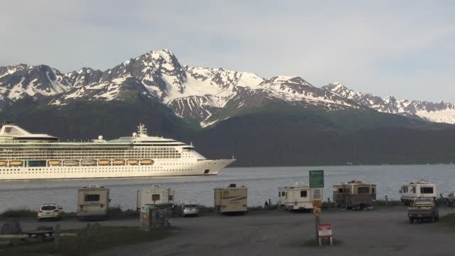 vídeos y material grabado en eventos de stock de driving shot of cruise ship leaving seward passing rv park with snowcapped mountain in the background - embarcación de pasajeros