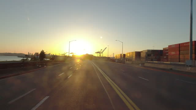 driving shot of leaving the harbour at sunset. oakland seaport is gearing up to meet the demands, the truck is busy transporting containers in... - dusk stock videos & royalty-free footage