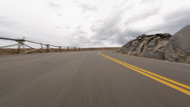 driving shot of mountain road against cloudy sky at rocky mountain national park - mountain road stock videos & royalty-free footage