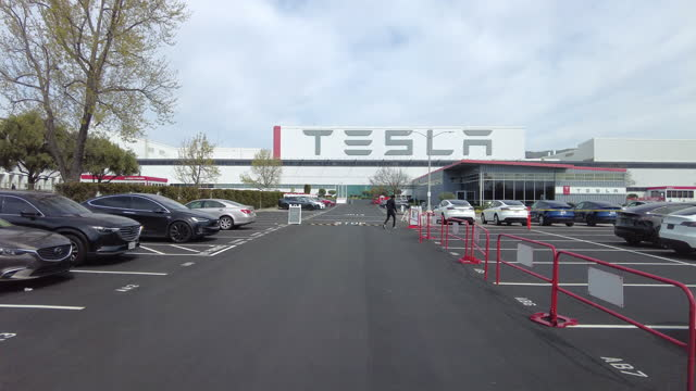 driving shot of people wearing face mask walking in the tesla car delivery parking lot amid the covid-19 pandemic in palo alto, california on march... - dolly shot stock videos & royalty-free footage
