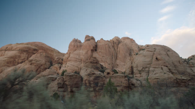 driving shot of sandstone rock formations near moab on scenic utah byway. - 岩層点の映像素材/bロール