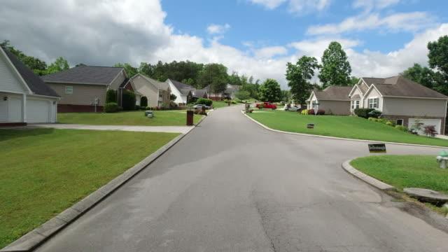vídeos y material grabado en eventos de stock de driving shot of subdivision homes in the suburb of usa during the 2020 global covid-19 virus pandemic - suburbio zona residencial