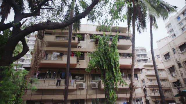 SLO MO. Driving shot past Mumbai apartment buildings with clothes hanging on the lines.