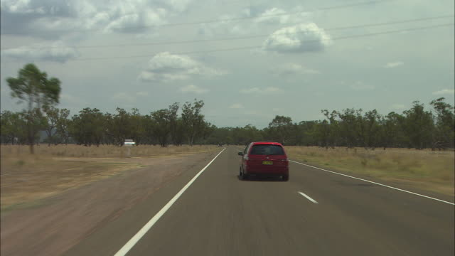 driving shot point of view front window - flat straight single carriageway bitumen road with barren landscape with sparse trees - overtaken by... - car point of view stock videos & royalty-free footage