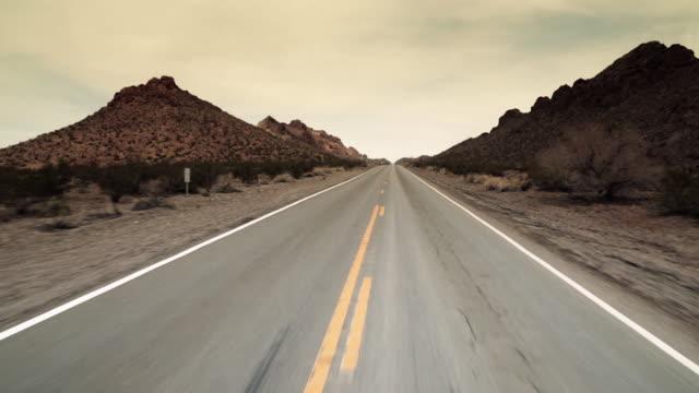 vidéos et rushes de driving shot through desert mountain pass - macadam