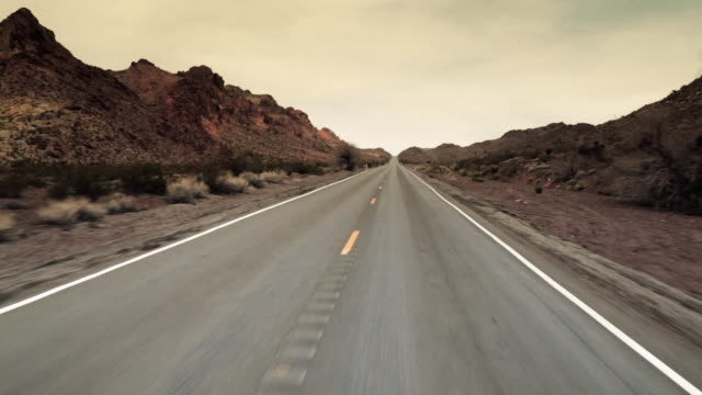 driving shot through desert mountain pass - empty road stock videos and b-roll footage