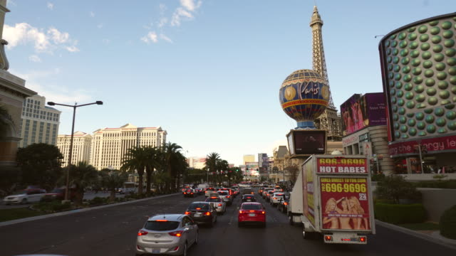 driving pov of the las vegas strip featuring paris hotel and hot babes advertisement on moving vehicle, daytime - replica della torre eiffel video stock e b–roll