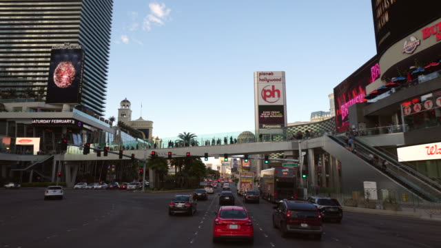 Driving POV of the Las Vegas strip featuring Planet Hollywood, and Paris hotels, daytime