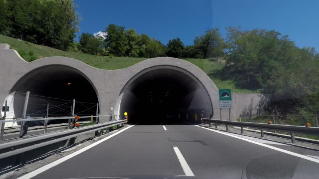 vidéos et rushes de driving through a modern road tunnel into sunlight, car travel, road trip in italy - car point of view