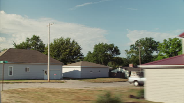 Driving through a small rural town with houses and a closed gas station