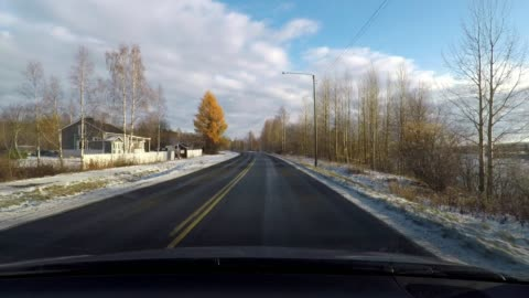 driving through a snow covered forest on a treelined highway, car travel, road trip in finland - finland stock videos & royalty-free footage