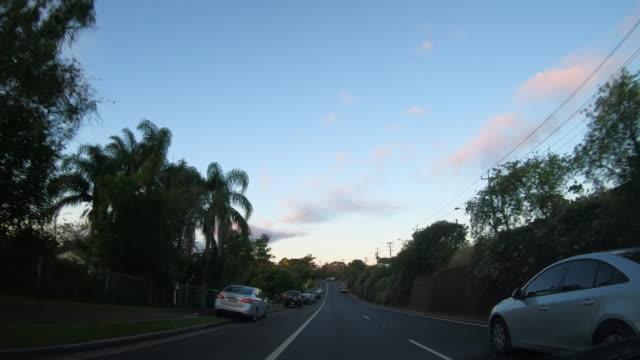 guidare attraverso una città al tramonto - macchina da presa manuale video stock e b–roll