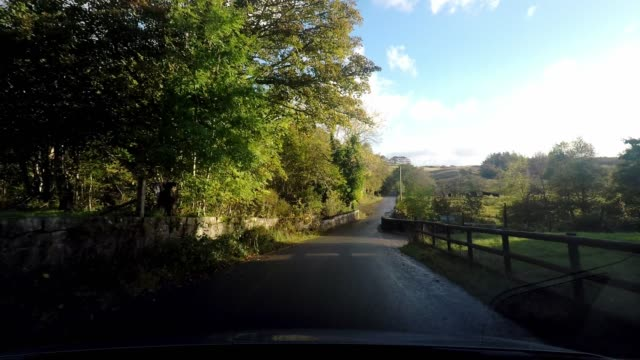 Driving through an idyllic country village with white houses, tree lined road, Isle of Skye, Scotland