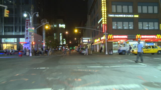 POV Driving through Broadway's thoroughfare of brightly lit signs and bustling city life / New York City, New York, United States