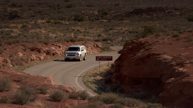 SUV driving through curved road in Arches National Park