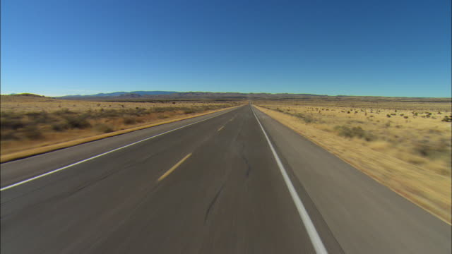 SIDE POV Driving through desert landscape, mountains in distance, near El Paso, Texas, USA