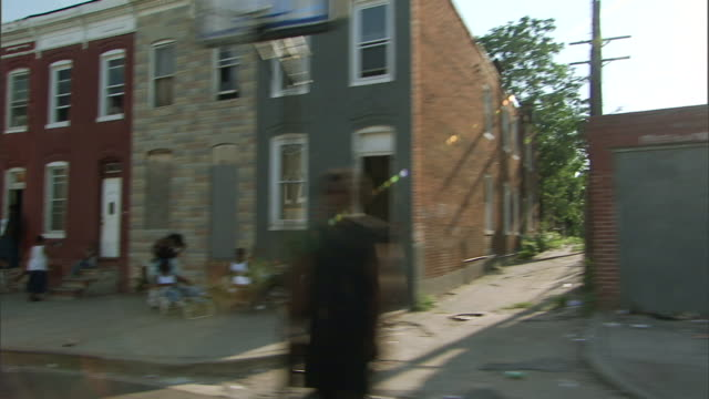 hd driving through low income blighted neighborhood passing residential short block black africanamerican people in front of house one boarded up... - baltimore maryland bildbanksvideor och videomaterial från bakom kulisserna