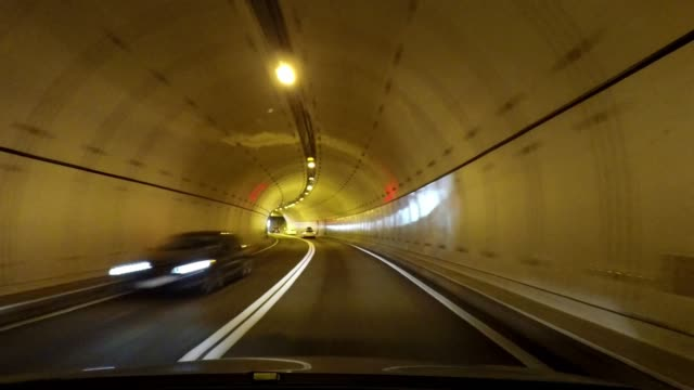 driving through modern tunnel, car travel, road trip in switzerland - dividing line stock videos & royalty-free footage