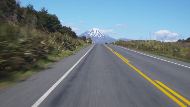 vídeos de stock, filmes e b-roll de pov, driving through rangipo desert, mount ngauruhoe in distance, tongariro national park, central north island, new zealand - 30 segundos ou mais