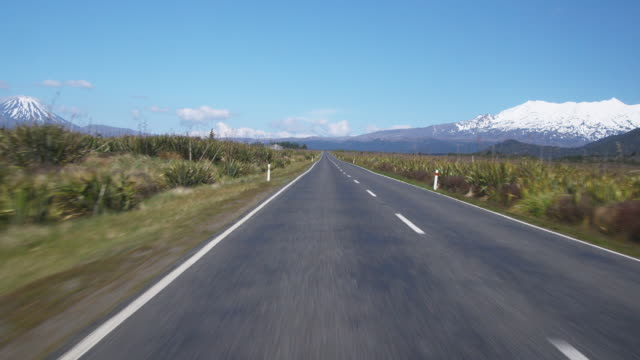 vídeos y material grabado en eventos de stock de pov, driving through rangipo desert, snow capped mountain in distance, tongariro national park, central north island, new zealand - punto de fuga