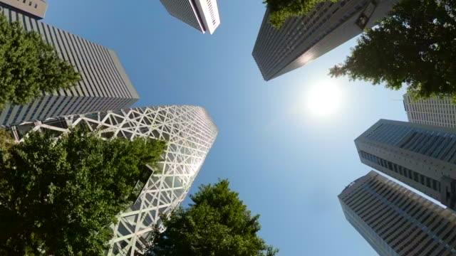 stockvideo's en b-roll-footage met rijden door wolkenkrabbers in de stad. draai en het kijken omhoog mening van wolkenkrabbers en groene bomen. - kantoorgebouw